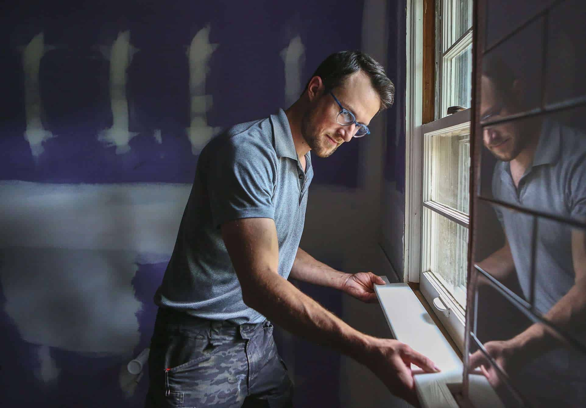 Nathan Spearing fits the sill of a window in an in-progress remodel.