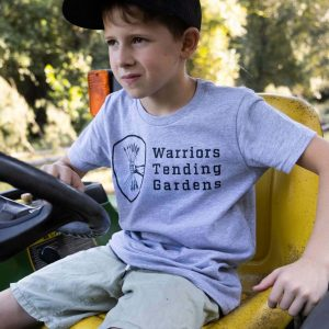 A boy sitting on a tractor wearing a Warriors Tending Gardens shirt and hat.