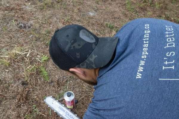 A man wearing a Warriors Tending Gardens shirt while starting a chainsaw.
