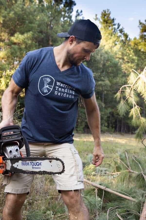 A man wearing a Warriors Tending Gardens shirt while using a chainsaw.