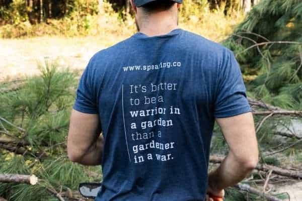 A man standing in a field wearing a Warriors Tending Gardens shirt.