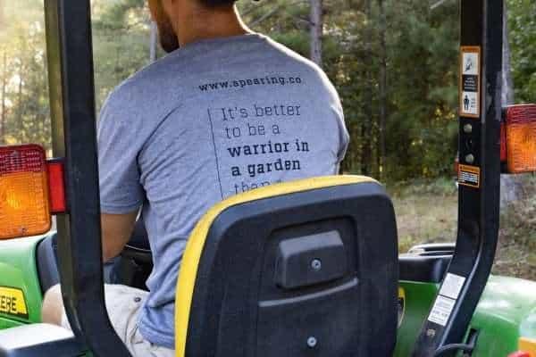 Man siting on a tractor wearing a Warriors Tending Gardens shirt.