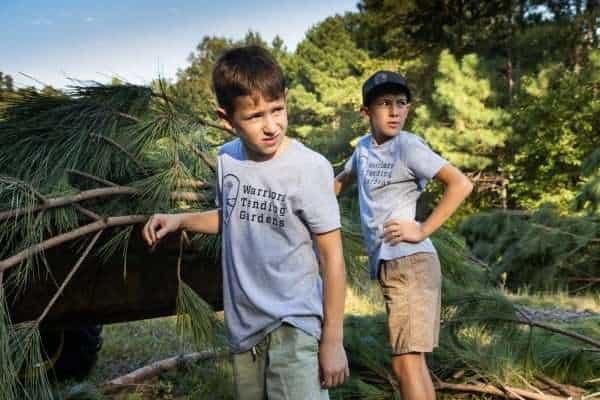 Two boys wearing Warrior Tending Gardens shirts.