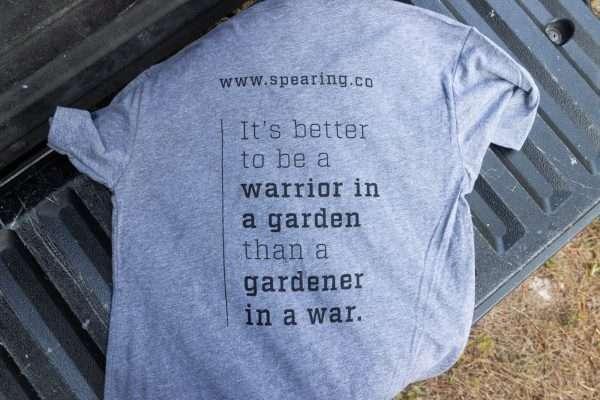 """Warriors Tending Gardens adult shirt in grey. Reads """"It's better to be a warrior in a garden than a gardener in a war."""""""