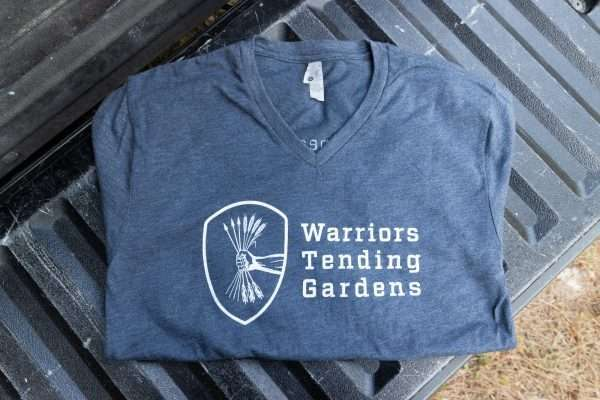 Warriors Tending Gardens adult shirt in navy. Front features the shield logo.