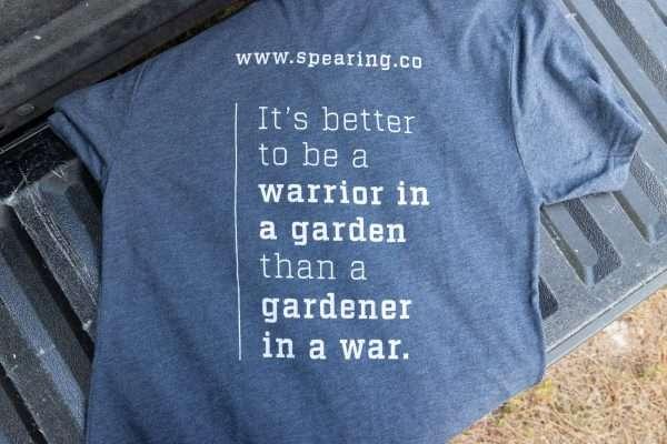 """Warriors Tending Gardens adult shirt in navy. Reads """"It's better to be a warrior in a garden than a gardener in a war."""""""