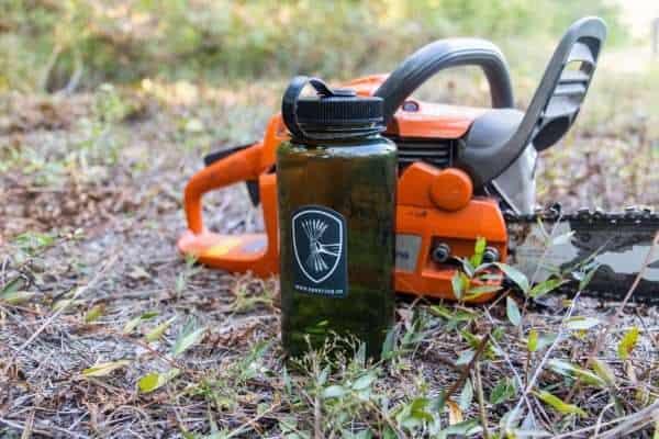 Warriors Tending Gardens sticker on a water bottle in a field.