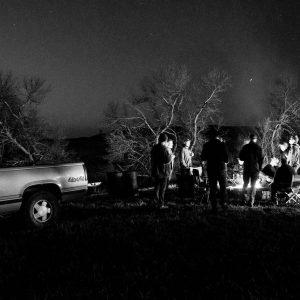 Men standing around a campfire under a starry night sky.